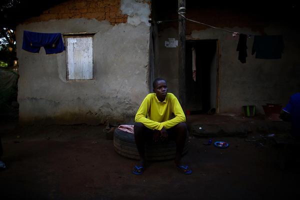 Alusine Banguar, 15, sits outside his home to explain his symptoms to a surveillance officer.