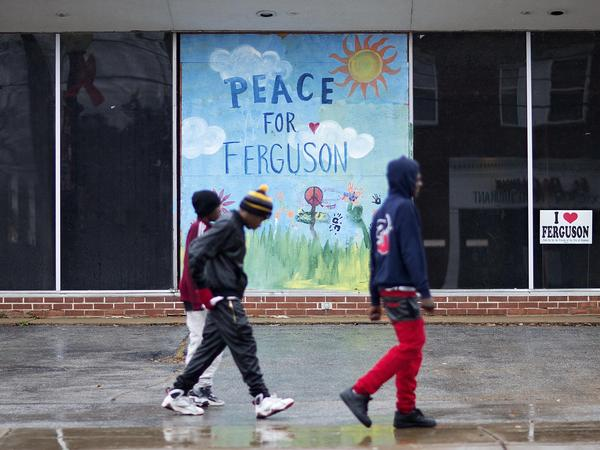 Youths walk past a mural depicting peace in Ferguson on a vacant building up the street from the city's police department.