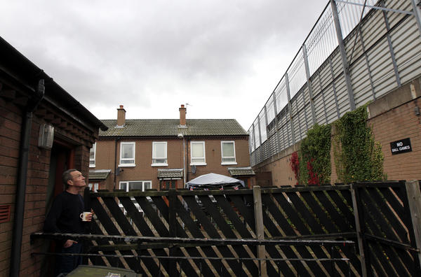 Retiree William Boyd looks at the peace wall that runs along the bottom of his garden in east Belfast, in 2012.