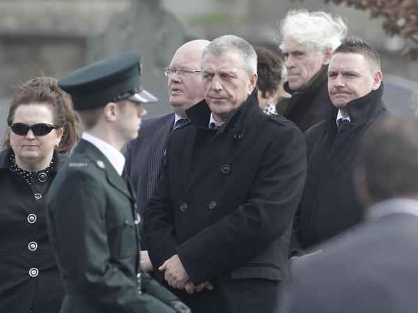 "Jackie McDonald (center), is  shown here at a funeral in 2011. He once ran the Ulster Defence Association, the biggest Protestant paramilitary group in Northern Ireland. Now, he works for a group that seeks peace. But he says many young people don't seem to want resolution: ""They've heard stories about their grandfather or their uncle. So these young people think they've missed out."""