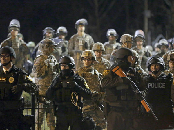 Police and Missouri National Guardsmen stand guard as protesters gather in front of Ferguson Police Department on Friday. Authorities made 15 arrests amid largely peaceful protests.