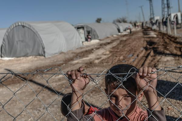 A Syrian Kurdish child looks through the fence of a refugee camp in the town of Suruc, Turkey, last month. The advance of Islamic State jihadists on Kobane has forced some 200,000 refugees to flee across the border to Turkey.