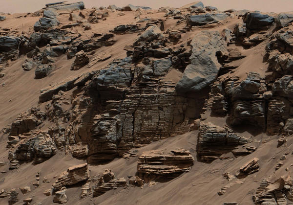"""Layers of rock in this image taken at the edge of """"Hidden Valley"""" on Mars suggest """"a lake-floor sedimentary deposit not far from where flowing water entered a lake,"""" NASA says."""