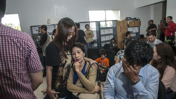 Family members of passengers of AirAsia flight QZ8501 gather at Juanda International Airport in Surabaya, Indonesia, on Sunday, hours after news broke that the flight had gone missing. The AirAsia Airbus plane with 162 people on board went missing en route from Indonesia to Singapore.