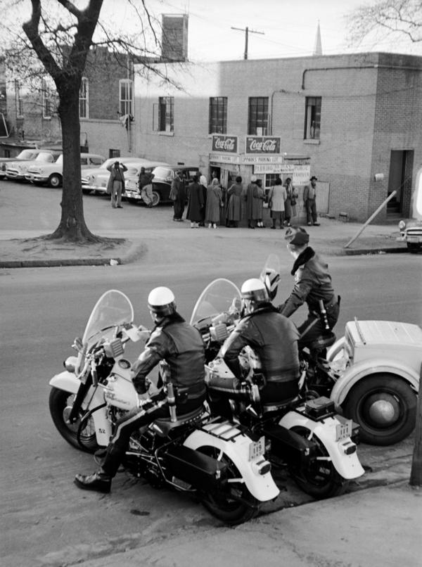 Police watch a crowd of African-Americans as they wait for a car pool lift in 1956 during the Montgomery Bus Boycott.