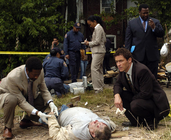 Detectives Lester Freamon (Clarke Peters, left) and Jimmy McNulty (Dominic West) kneel beside a body, befuddled.