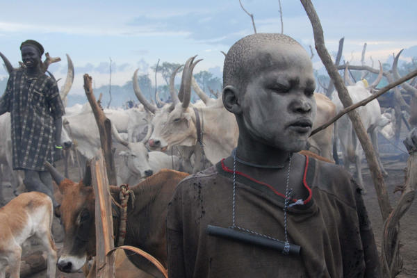 This young herder has lots of protection. The ash on his face isn't just decorative; it keeps away flies. The filter in his pipe removes tiny crustaceans carrying Guinea worm larvae from drinking water.