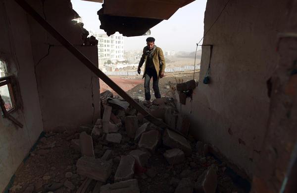 A Yemeni man walks amid the debris inside a heavily damaged house near the presidential palace on Tuesday.