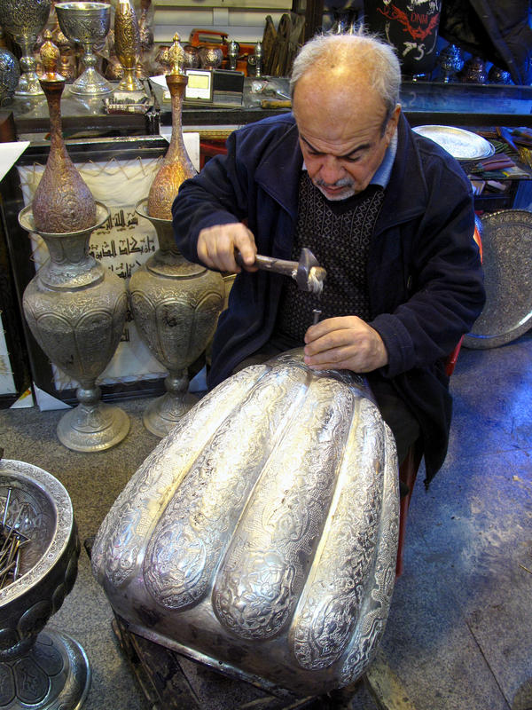 Asghar Pourheydar-Shirazi uses a hammer and a nail to engrave intricate patterns on a vase at his shop in Isfahan. He was optimistic following the country's 1979 revolution, but says the economy has fared poorly for decades. At 64, he works 10 to 12 hour days.