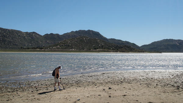 """Marty Gabriel, a retired truck driver, passes his metal detector over the exposed sand at California's Lake Perris. Gabriel has been visiting the lake for 25 years. """"We definitely need rain,"""" he says."""