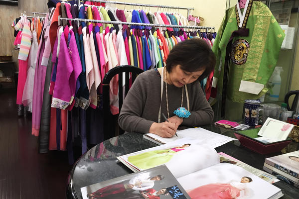 Youjung Jung takes a customer's order for a new outfit at her store Hanbok Story in Queens, N.Y.