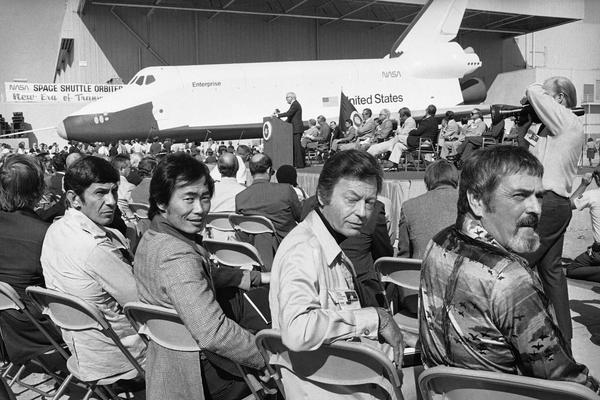 The space shuttle is shown in the background after its unveiling in Palmdale, Calif., in September 1976. In the foreground is the crew of the television series <em>Star Trek</em>, whose ship was also named Enterprise. They are Leonard Nimoy (from left), who portrayed Mr. Spock; George Takei, who played Mr. Sulu; DeForest Kelley, who played Dr. McCoy; and James Doohan, who played Scotty.
