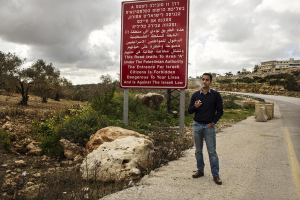 Shlomy Mizrahi, an Israeli real estate agent, stands near a sign at the entrance to a Palestinian village in the West Bank. The Israeli government bars Israelis from entering the Palestinian towns for their safety. Mizrahi lives in the nearby Israeli settlement of Ariel and sells homes there.