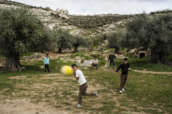 Palestinian children play in Marda, with the Jewish settlement of Ariel on the ridge in the background. Prior to the late 1970s, the land on which Ariel sits was farmed by nearby Palestinian families.