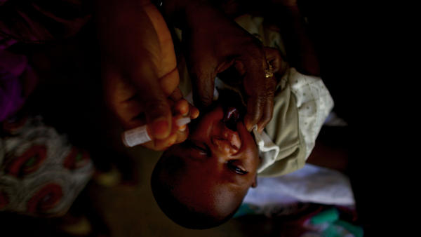 Two drops of polio vaccine are administered to a child in a Nigerian health clinic.