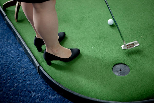A staffer participates in the annual Democrats vs. Republicans putting challenge.