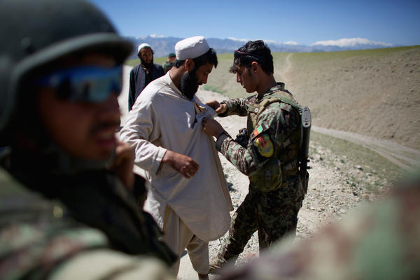 An Afghan army soldier frisks a man who claims to be an Afghan policeman. After questioning, and producing an ID, he was released. None of the 10,000 U.S. military personnel are present as the Afghan army fights in the eastern province of Nangahar, a notorious Taliban bastion near the border with Pakistan.