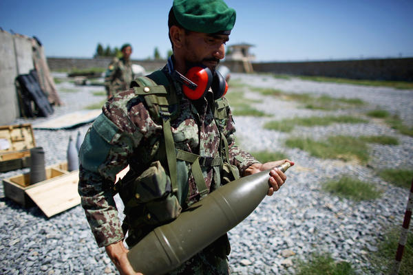 A soldier carries a shell to a Soviet-era artillery gun. Afghan officers say the Taliban not only cross the border, they hide in the villages, dropping their weapons and picking up a shovel when the soldiers appear.