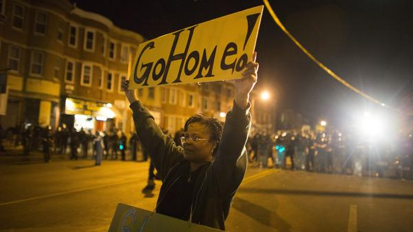A woman in Baltimore holds a sign Tuesday night telling protesters to go home; a curfew and community intervention are being credited with helping ease tensions in the city.