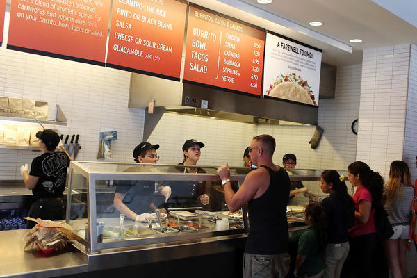 Chipotle restaurant workers in Miami fill orders on April 27, the day the company said it would  use only non-GMO ingredients in its food.