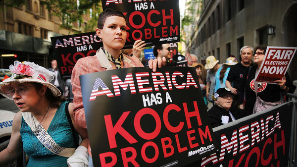 """Can candidates courting billionaires count as corruption, even if there are no explicit strings attached? Some activists see the campaign contributions of the super-rich as a problem, regardless of whether """"quid pro quo"""" deals are made. Here, activists protest the political influence of the wealthy Koch Brothers near David Koch's Manhattan apartment on June 5, 2014."""