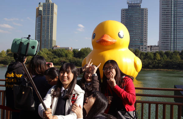 South Koreans take a selfie near a giant yellow rubber duck in Seokchon Lake on October 15, 2014 in Seoul, South Korea. (Chung Sung-Jun/Getty Images)