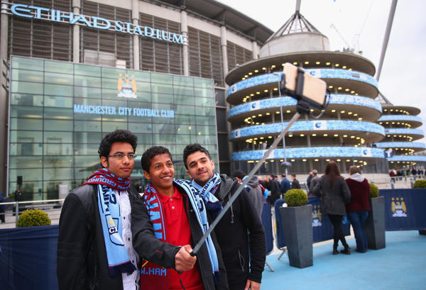 Football fans take a photo with a selfie stick ahead of the Barclays Premier League match between Manchester City and West Ham United at Etihad Stadium on April 19, 2015 in Manchester, England.  (Clive Brunskill/Getty Images)