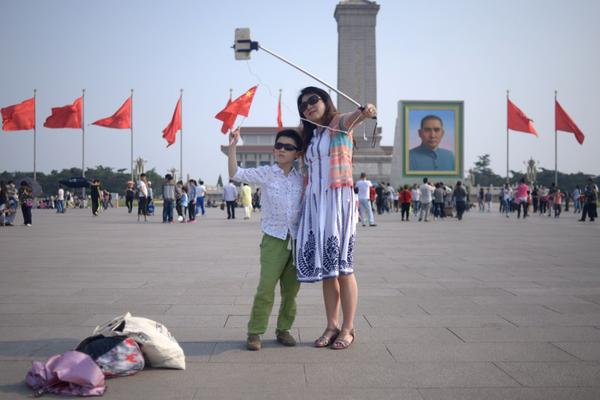A couple check a selfie stick as they prepare to take a photo at Tiananmen square in Beijing on April 30, 2015. (Wang Zhao/AFP/Getty Images)