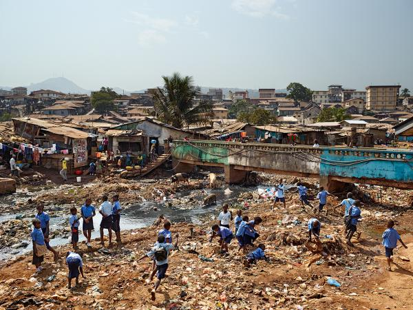A contaminated river runs through the valley in Freetown, Sierra Leone, where there is neither sanitation nor garbage collection. Children from the nearby Kroo Bay primary school play amid the trash.