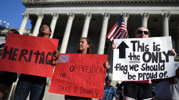 Protesters close their eyes in silent prayer as they stand on the South Carolina Statehouse steps during a rally to take down the Confederate flag, Saturday, June 20, 2015, in Columbia, S.C.