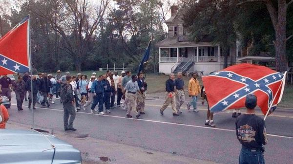 "The ""Get In Step"" marchers pass by a small group of Confederate Flag supporters Tuesday, April 4, 2000, near Wells, S.C., on their way to Orangeburg on the third day of the march to Columbia to have the flag taken down from the Statehouse."