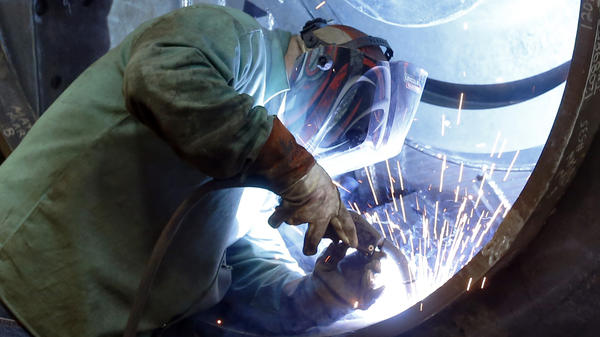 A worker welds parts in fans for industrial ventilation systems at the Robinson Fans Inc. plant in Harmony, Pa., in February. Hourly wages in the U.S. remained unchanged last month.