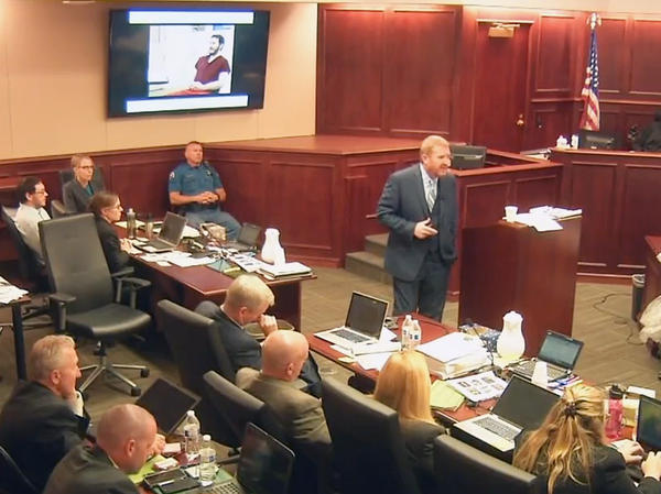 In this image taken from video, James Holmes (upper far left) listens to defense attorney Daniel King give closing arguments during Holmes' trial in Centennial, Colo., on Tuesday. Holmes was found guilty Thursday of first-degree murder in the deaths of 12 people at a Colorado theater.