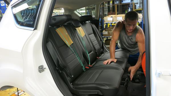 A worker at Ford's assembly plant in Wayne, Mich., installs back seats made from soy-based foam in a Ford C-Max.