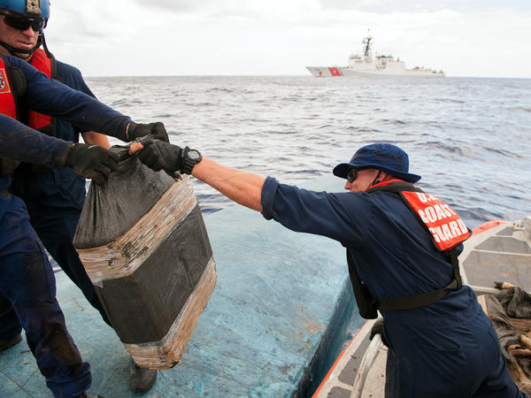 In this July 19 photo released by the U.S. Coast Guard, a crew removes some of the 12,000 pounds of cocaine seized from a semi-submersible vessel in Pacific waters south of Mexico.
