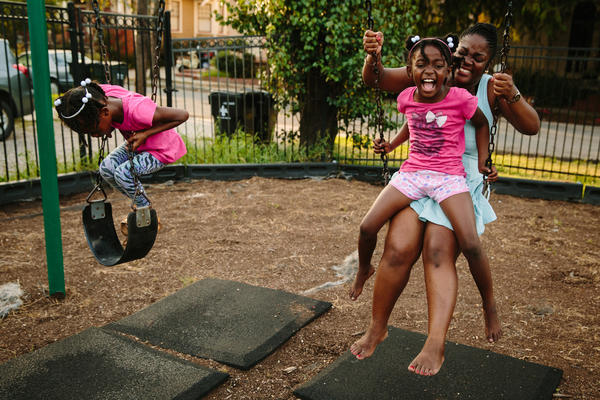 Briceshanay Gresham laughs with her daughter Uri (wearing shorts) and sister Dyha. Ten years after escaping Katrina, Gresham teaches elementary school in New Orleans and is studying to become a music therapist.