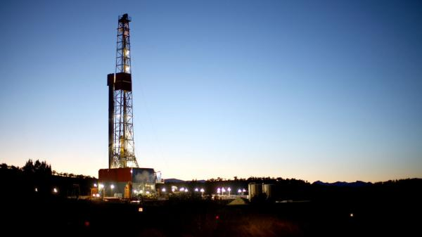 A natural gas drilling rig's lights shimmer in the evening light near Silt, Colo.