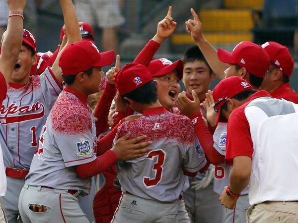 Japan celebrates after erasing an eight-run deficit to win the Little League World Series Championship baseball game, 18-11.