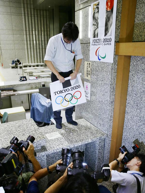 An official of Tokyo's metropolitan government removes a poster bearing logos for the Tokyo Olympic and Paralympic Games from a wall Tuesday.