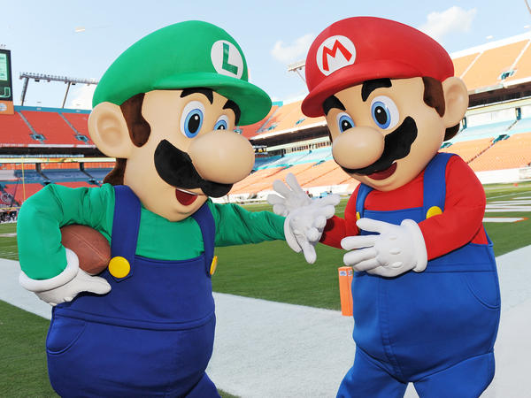 Mario (right) and his brother Luigi, pictured before a college football game in 2014 in Florida, are the iconic characters from <em>Super Mario Bros.</em> video game franchise.