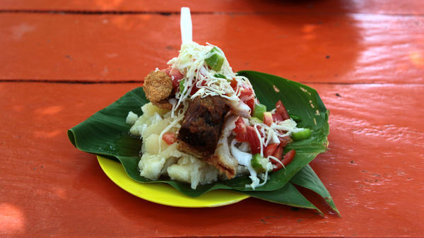 Vigorón served at El Gordito in Granada, Nicaragua. The combination of soft, starchy yucca; salty, rough pork cracklings; and tangy, cool slaw made with cabbage, onions, tomato, <em>mimbre</em> fruit (also known as <em>mimbro)</em>, chile and vinegar offers a distinct interplay of textures and flavors.