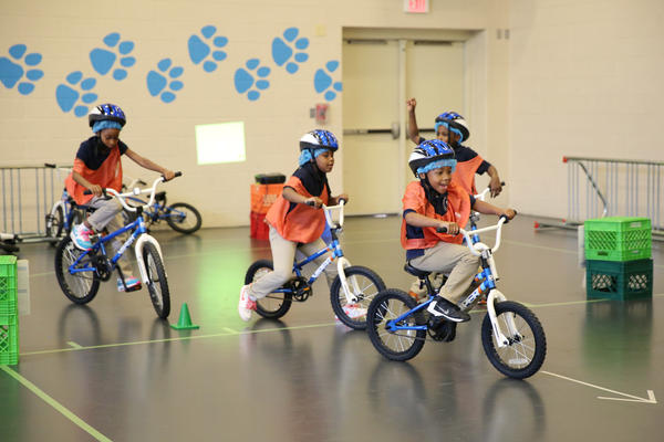 Second-graders ride in circles around the school's indoor gym.