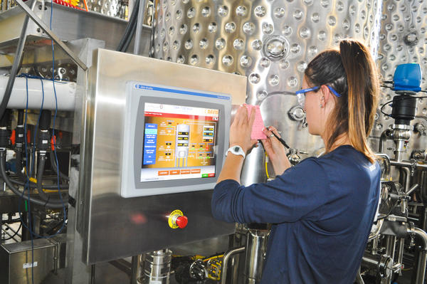 A student records information about a wine tank's sugar levels and juice temperatures on a computer screen inside UC Davis' research winery. In the future, students will also be able to monitor information about Clean in Place processes (which save water) using these screens.