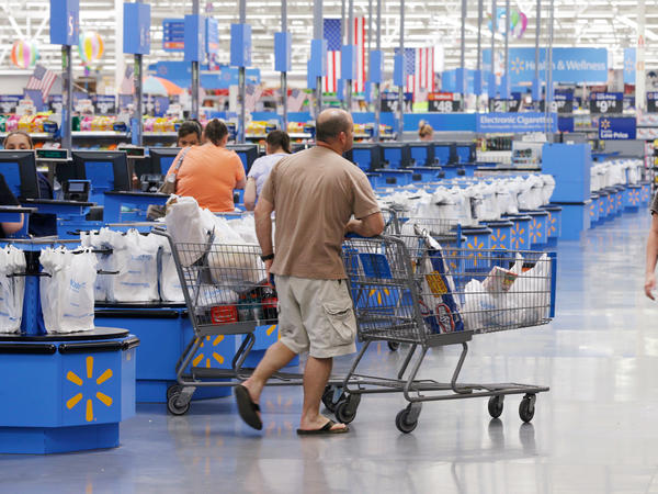 Shoppers walks from the checkout at a Wal-Mart Supercenter store in Springdale, Ark., Thursday, June 4, 2015.