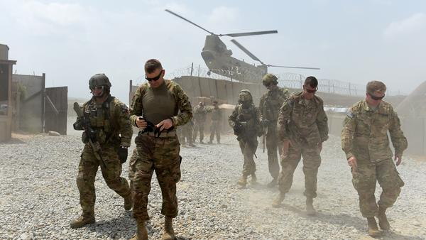 U.S. Army soldiers walk as a NATO helicopter flies overhead at coalition force Forward Operating Base (FOB) Connelly in the Khogyani district in the eastern province of Nangarhar on August 13, 2015.