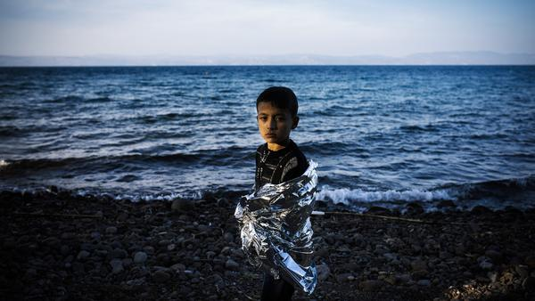 A boy stands onshore after arriving with other refugees and migrants on the Greek island of Lesbos, after crossing the Aegean Sea from Turkey, on Saturday.