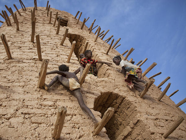 "Friends play on the main minaret of the Grand Mosque in Bani, Burkina Faso, during the Muslim holiday<strong> </strong><a href=""http://hereandnow.wbur.org/2015/07/17/muslim-call-to-prayer"">Eid al-Fitr.</a>"