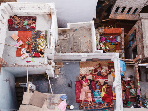 Families sleep on rooftops in Varanasi, India, to escape the summer heat.