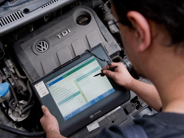 A service technician uses a diagnostic device in front of a diesel engine in a Volkswagen Touran in an auto repair shop in Hanover, Germany. Researchers have been pushing for freedom to learn more about the code inside cars in the fallout of the VW software-rigging scandal.