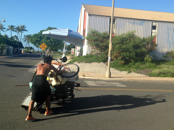 A homeless man who had been living in a large encampment in the Kakaako neighborhood of Honolulu pushes his belongings away as city officials sweep the area on Oct. 8. Honolulu city crews cleared the final section of one of the largest homeless encampments in the nation, once home to hundreds of people.